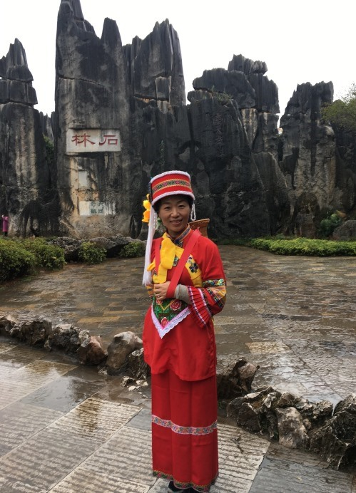 At the famous Stone Forest of Shilin National Park in China, wearing the traditional dress of the Yunnan province.